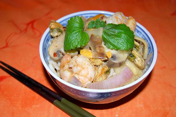 Meeresfrüchte mit Bratreis und Gemüse, im Schälchen angerichtet mit Stäbchen