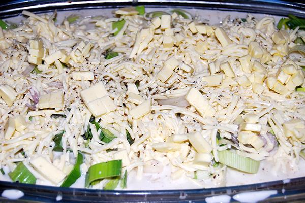 Das Gemüse in der Auflaufform, mit der Sahnemischung übergossen und Butterstückchen überzogen