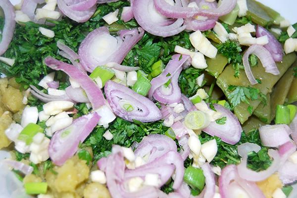 Der Salat mit Kräutern und Schalotten, Knoblauch und Lauchzwiebeln kur vor dem Anmachen mit dem Dressing