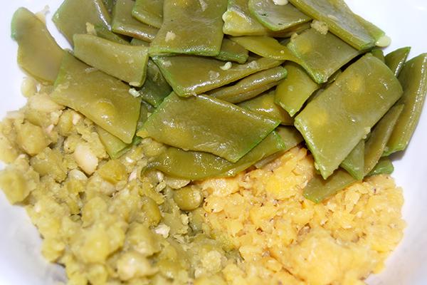 Gekochte Bohnen (oben), gekochte getrocknete Erbsen (links) und gekochte, leicht zerfallene Linsen (rechts)