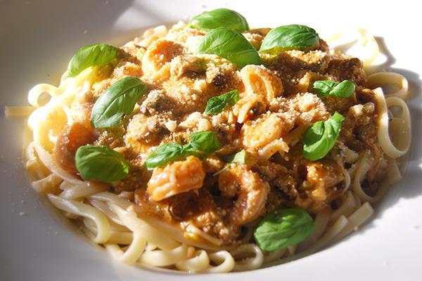 Meeresfrüchte auf Bavette serviert, mit Pinienkernen, Parmesan und Basilikum garniert