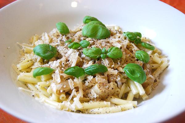 Pasta mit Senf-Sauce, garniert mit Parmesan und Basilikum