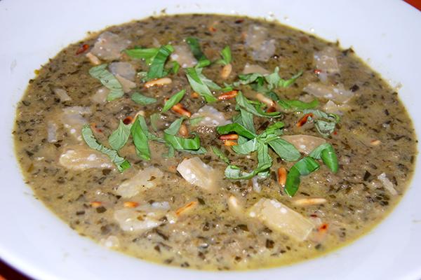 Spinat-Zucchini-Aubergine-Suppe, mit Pinienkernen, Parmesan und Basilikumstreifen garniert