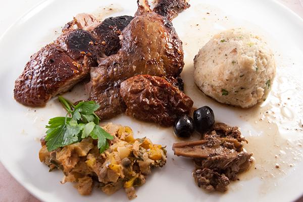 Gefüllte Ente angerichtet, mit Füllung, Tomate, Oliven, Pilze, Semmeknödel und Sauce