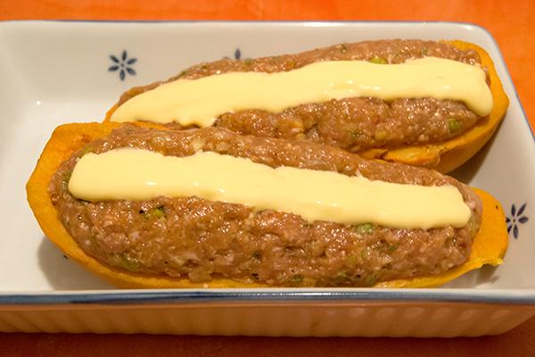 Ausgehöhlte Süßkartoffel-Hälften mit Hackfleischmasse und Schmelzkäse vor dem Backen