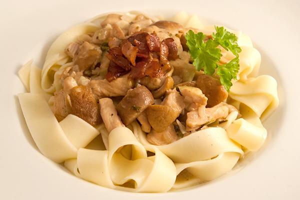 Hähnchenbrustgeschnetzeltes mit Steinpilzen und knusprigen Speckstreifen auf Pasta