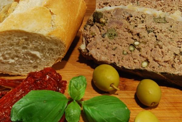 Landpastete, angerichtet mit Baguettebrötchen, getrockneten Tomaten, Oliven und Basilikum