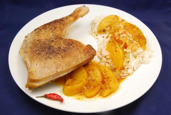 Entenschenkel, Pfirsichspalten, Reis und aromatische Sauce