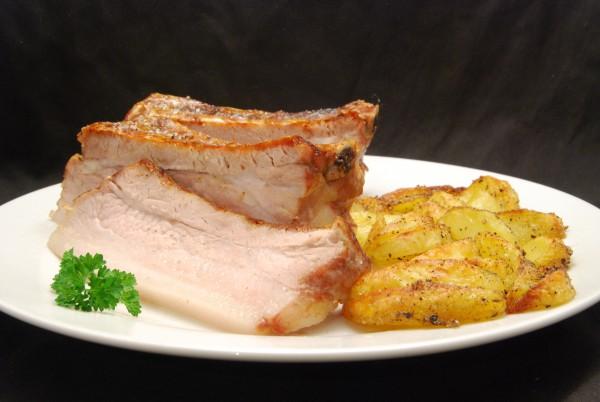 Gegrillte Schweinebauchscheiben und Kartoffelspalten
