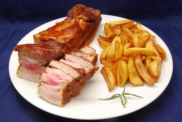 Saftiger, wohlschmeckender Schweinebauch – noch leicht rosé - mit Kartoffelspalten