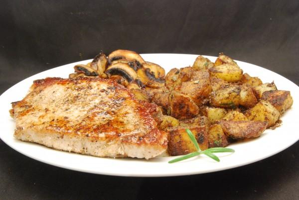 Leckeres Schweinekotelett mit Kartoffeln und Pilzen