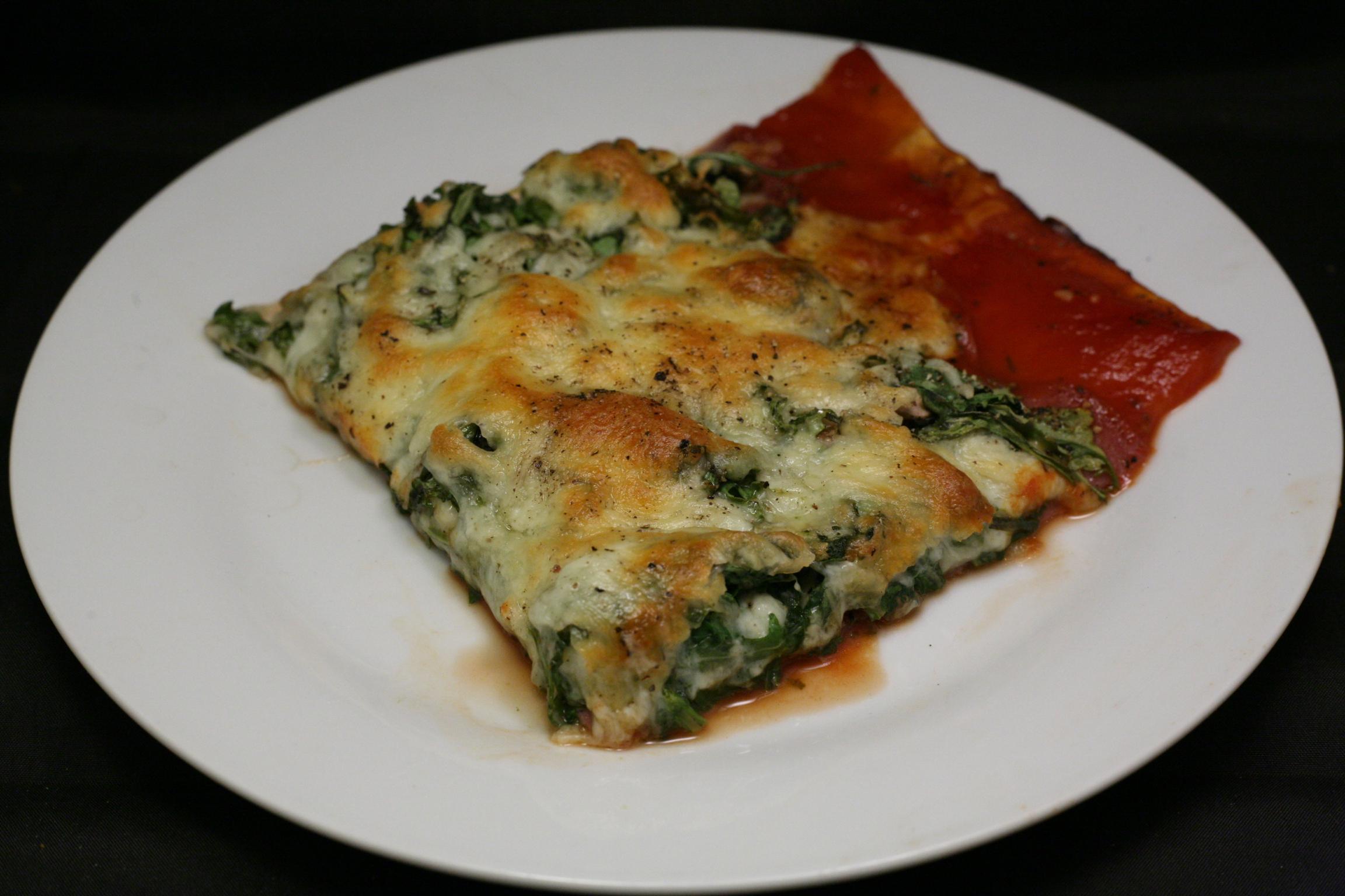 Pizza mit Rucola, Salami, Champignons und Oliven